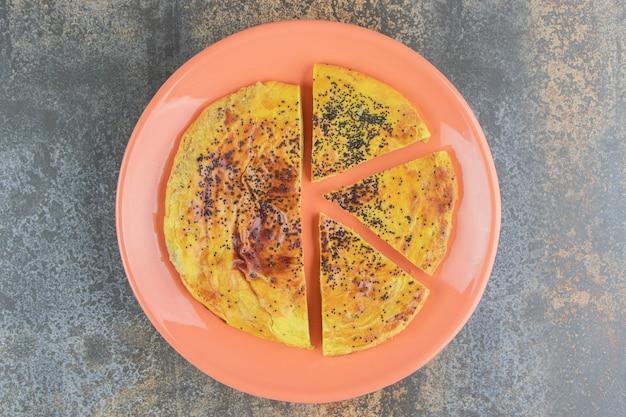 Okrągłe ciasto z makiem na pomarańczowym talerzu