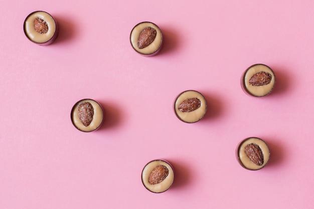 Okrągłe czekoladki z kremem pistacjowym i solonymi migdałami na różowym stole. leżał płasko