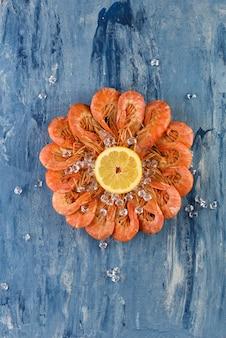Okrągłe czerwone krewetki z cytryną i lodem. niebieskie tło malowane porysowany. widok z góry owoce morza. skopiuj miejsce krewetki z cytryną gotowe do spożycia.