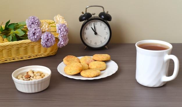 Okrągłe domowe ciasteczka na talerzu obok filiżanki herbaty i budzika