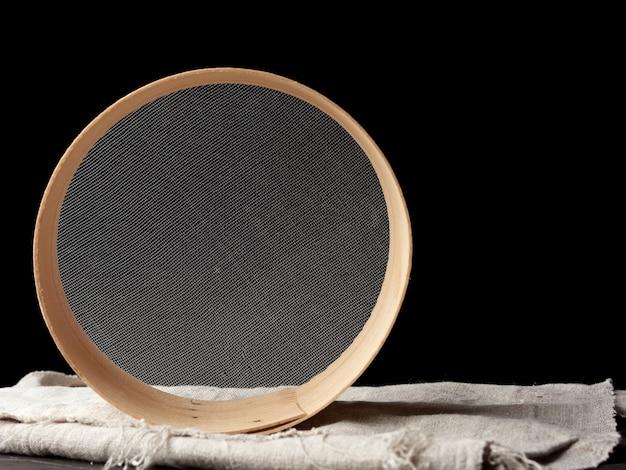 Okrągłe drewniane sito na czarnym tle, przestarzałe przybory kuchenne