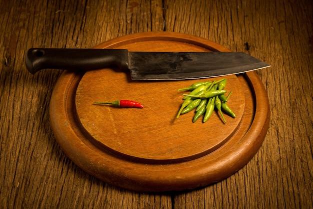 Okrągłe drewno deska do krojenia. papryka chili zielona i czerwona. nóż