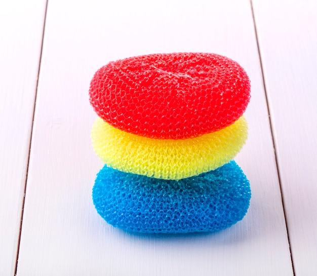 Okrągłe gąbki do mycia naczyń w różnych kolorach umieszczone na białym drewnianym stole
