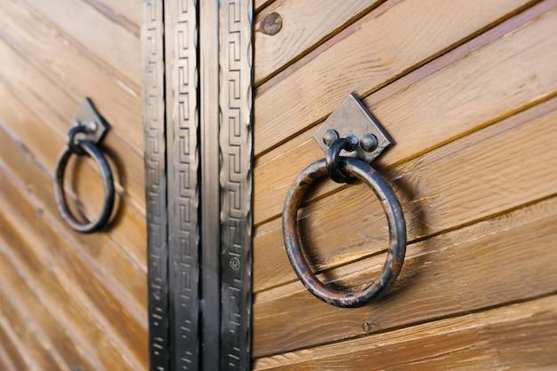 Okrągłe klamki kute na drzwiach drewnianych