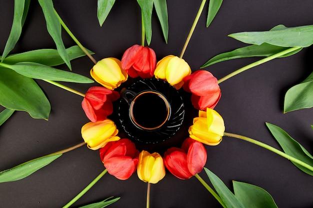 Okrągłe koło czerwone i żółte tulipany i filiżankę kawy