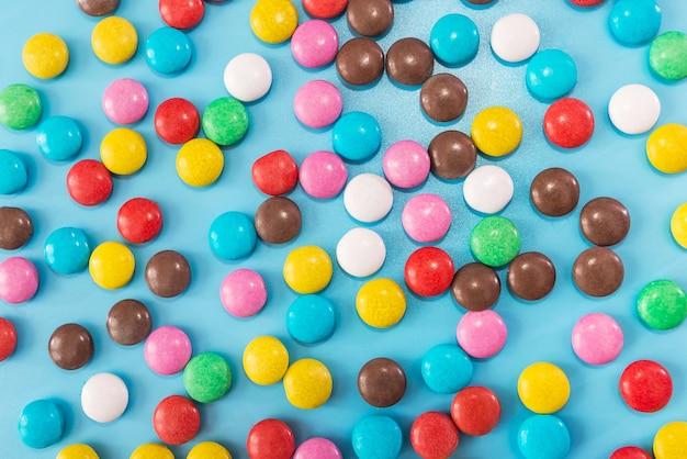 Okrągłe kolorowe cukierki na niebieskim tle. cukierki kolorowe tło, tekstura.