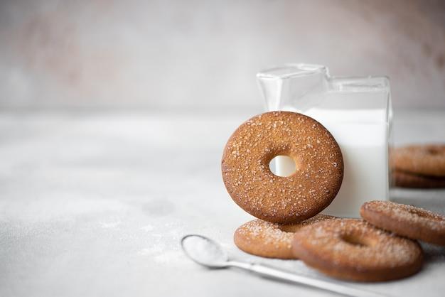 Okrągłe kruche ciasteczka z cukrem i zimnym mlekiem na białym stole