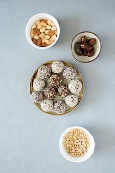 Okrągłe kulki energetyczne słodycze z suszonymi owocami i orzechami na płaskim talerzu leżały na szarym tle