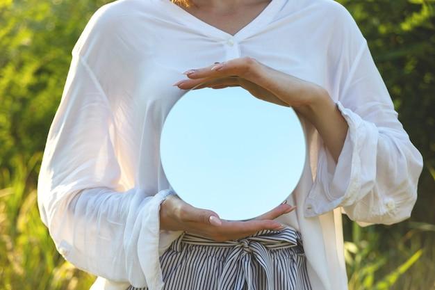 Okrągłe lustro w rękach kobiety, która pragnie być bliżej letniej natury