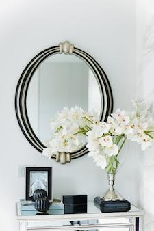 Okrągłe lustro z kwiatami na stole we wnętrzu salonu