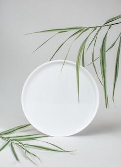 Okrągłe lustro z zielonymi liśćmi palmowymi na białym tle