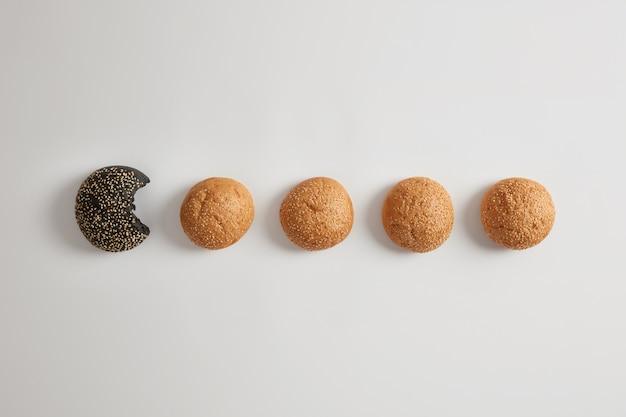 Okrągłe, małe, organiczne bułeczki do burgerów bez drożdży z sezamem na białej powierzchni. zdrowy produkt bezglutenowy. jeden czarny jest ugryziony. koncepcja fast food. piekarnia i żywienie. apetyczne bułeczki.