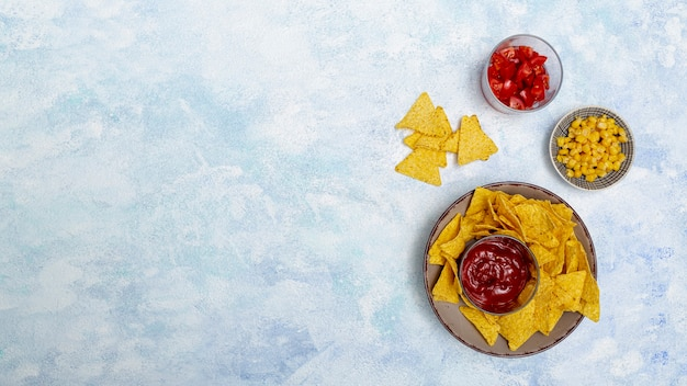 Okrągłe miski z sosem nachos, pomidorami kukurydzianymi