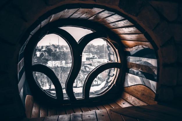 Okrągłe okno z drewnianym wykończeniem, z niezwykłą kratą, z widokiem na zaśnieżoną wioskę