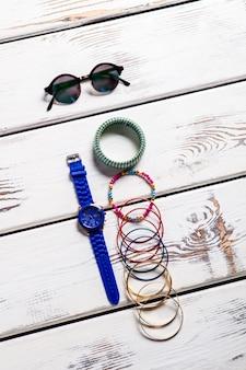 Okrągłe okulary i akcesoria damskie. kobiece akcesoria na drewnianym backround. ładne dodatki dla kobiet. mały i jasny.