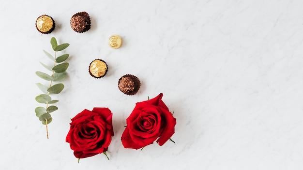 Okrągłe orzechowe czekoladki przy tapecie z czerwoną różą