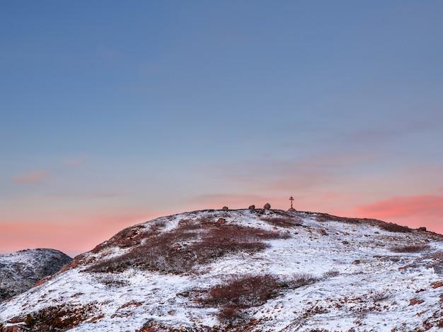 Okrągłe ośnieżone arktyczne wzgórza, minimalistyczny krajobraz polarny z drewnianym krzyżem na górze. półwysep kolski.