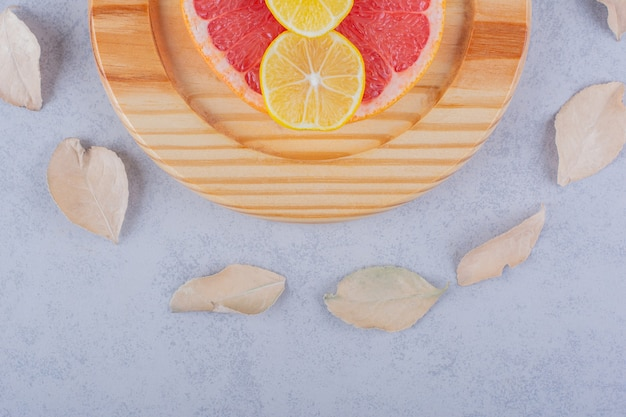 Okrągłe plastry świeżego grejpfruta i cytryny na drewnianym talerzu.