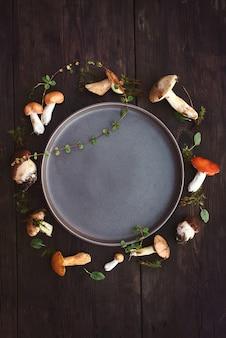Okrągłe ramki z różnych surowych grzybów leśnych na ciemnym tle. koncepcja zbiorów jesienią. leżał na płasko, rama grzybów