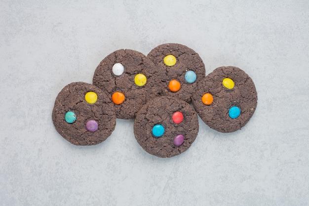 Okrągłe słodkie ciasteczka czekoladowe na białym stole.