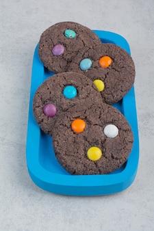 Okrągłe słodkie ciasteczka czekoladowe na niebieskim talerzu.