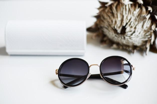 Okrągłe stylowe i modne okulary przeciwsłoneczne z etui i kwiatkiem na białym tle