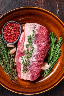 Okrągłe surowe mięso wołowe pokrojone do pieczenia na rustykalnym talerzu z ziołami. ciemne tło. widok z góry.