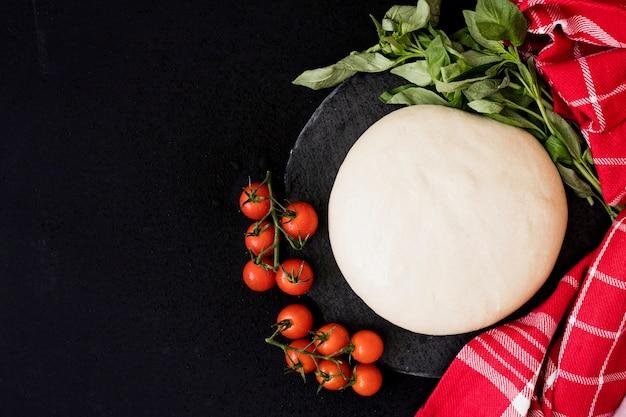 Okrągłe świeżo chlebowe ciasto; pomidory koktajlowe; bazylia i serwetka na czarnym tle