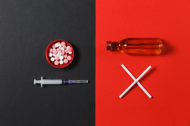 Okrągłe tabletki leków, pusta igła do strzykawki, butelka z alkoholem koniak, whisky, dwa skrzyżowane papierosy