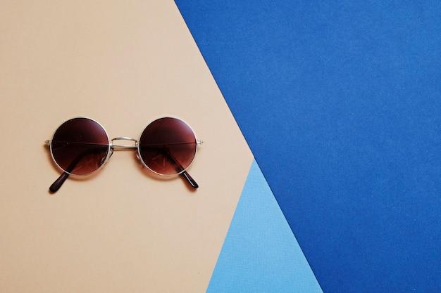 Okrągłe złote okulary przeciwsłoneczne w stylu retro na geometrycznym niebieskim i beżowym