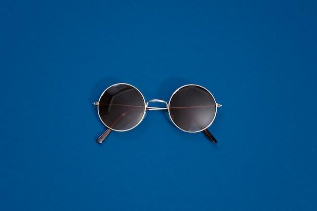 Okrągłe, złote okulary przeciwsłoneczne w stylu retro na klasycznym niebieskim