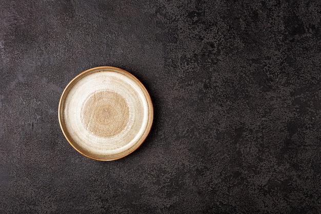 Okrągły beżowy talerz ceramiczny na ciemnym tle strukturalnym, widok z góry