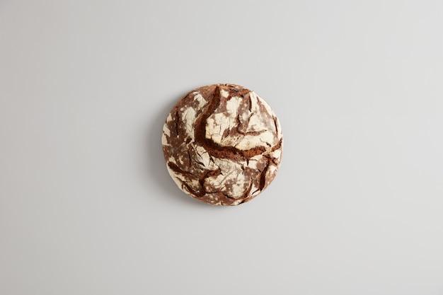 Okrągły bochenek chleba piekarniczego na białym tle na tle białego studia. produkt wypiekany w domu. naturalne stworzenie. chrupiący brązowy chleb borodino na zakwasie. organiczne prawidłowe odżywianie i koncepcja żywności