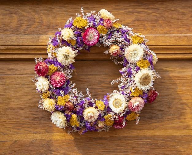 Okrągły bukiet kolorowych, żywych suszonych kwiatów na starych drewnianych drzwiach. jesienna dekoracja