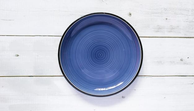 Okrągły ceramiczny pusty talerz ciemnoniebieski umieszczony na drewnianym stole czarno-biały tekstura tło, widok z góry, makieta dla menu danie w restauracji.