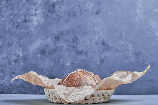 Okrągły chleb ręcznie robiony na kartce papieru.
