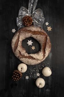 Okrągły chleb żytni z suszonymi owocami na czarno. świąteczne dekoracje, stylizacja zegara.