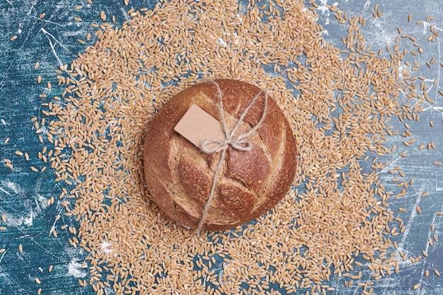 Okrągły ciemny chleb na niebieskim stole.