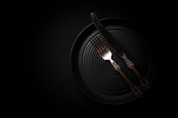 Okrągły czarny ceramiczny talerz z zabytkowymi sztućcami