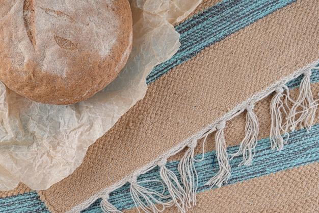 Okrągły domowy chleb wypiekany z mąki pełnoziarnistej.