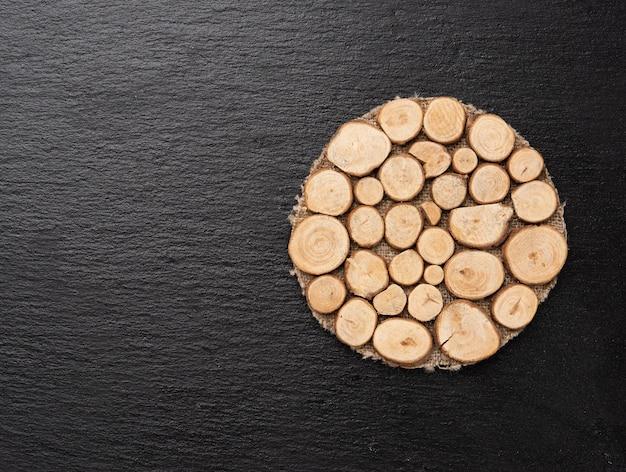 Okrągły drewniany stojak na czarnej powierzchni, widok z góry, miejsce na kopię
