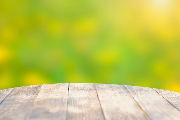 Okrągły drewniany stół i niewyraźne letnie tło. skopiuj miejsce