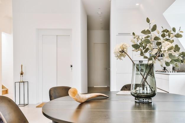 Okrągły drewniany stół ze szklanym wazonem z kwiatami i ozdobnym rogiem na tle białej kuchni