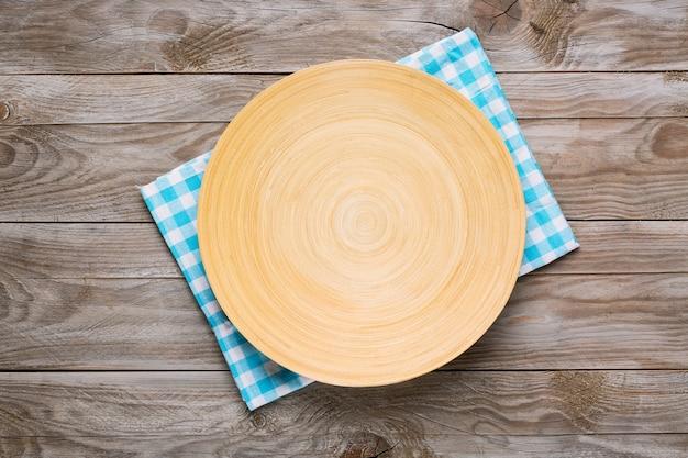 Okrągły drewniany talerz na drewnianym stole niebieski obrus w kratę. widok z góry. makieta do projektu żywności.