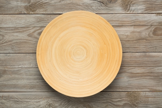 Okrągły drewniany talerz na drewnianym stole. widok z góry. makieta do projektu żywności.