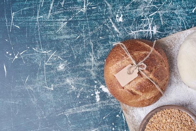 Okrągły gotowany chleb na niebieskim stole.