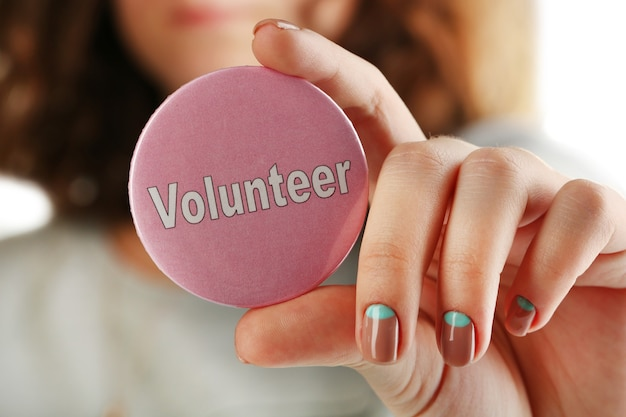 Okrągły guzik wolontariusza w dłoni