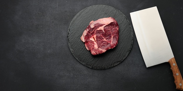 Okrągły kawałek surowego mięsa wołowego na czarnej tablicy. ribeye na grilla, widok z góry, miejsce na kopię