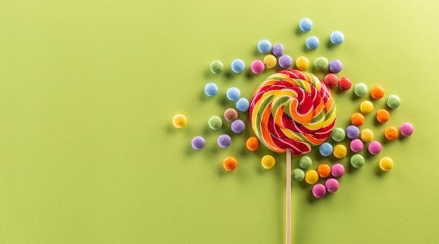 Okrągły lizak tęczowy na drewnianym patyku otoczony kolorowymi słodyczami o niesamowitym owocowym smaku.