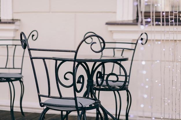 Okrągły metalowy stół i zabytkowe krzesła w ulicznej kawiarni